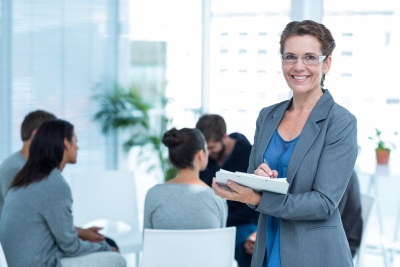smiling female therapist with group therapy in session